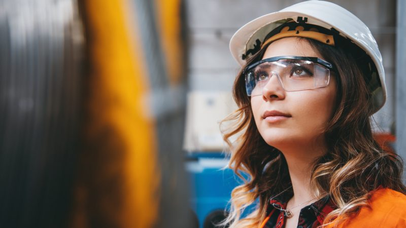 Portrait of young beautiful engineer woman working in factory building.